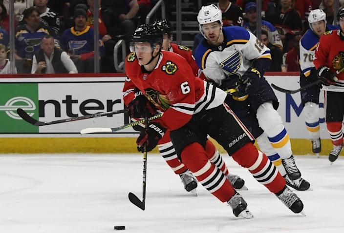 Chicago Blackhawks defenseman Olli Maatta (6) moves the puck away from St. Louis Blues left wing Zach Sanford (12) during the first period of an NHL hockey game between the Chicago Blackhawks and the St. Louis Blues on Sunday March 8, 2020, in Chicago. (AP Photo/Matt Marton)