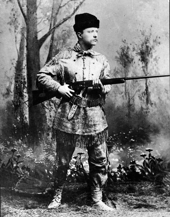 """A full-length studio portrait of Theodore Roosevelt (1858 - 1919), president of the United States from 1901 to 1909, wearing hunting gear and holding a Winchester gun in an artificial forest setting, circa 1900.<span class=""""copyright"""">Pictorial Parade/Getty Images</span>"""