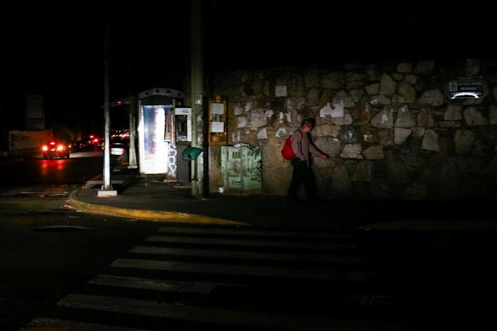 A man walks on a street during a power cut in Caracas, Venezuela, on March 27, 2019, as the country endures its second nationwide blackout in March 2019 (AFP Photo/Cristian Hernandez)