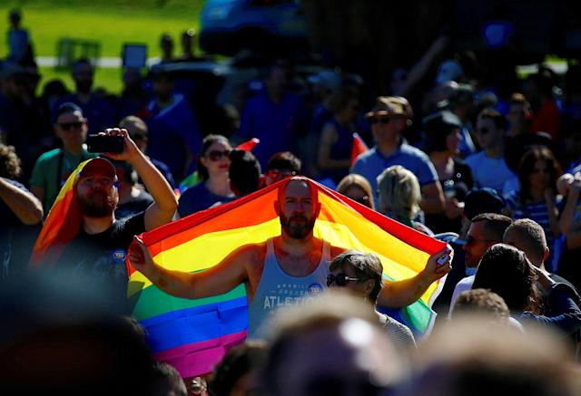<p>A supporter of the 'Yes' vote holds a colorful flag as he celebrates after it was announced the majority of Australians support same-sex marriage in a national survey, paving the way for legislation to make the country the 26th nation to formalize the unions by the end of the year, at a rally in central Sydney, Australia, Nov. 15, 2017. (Photo: David Gray/Reuters) </p>