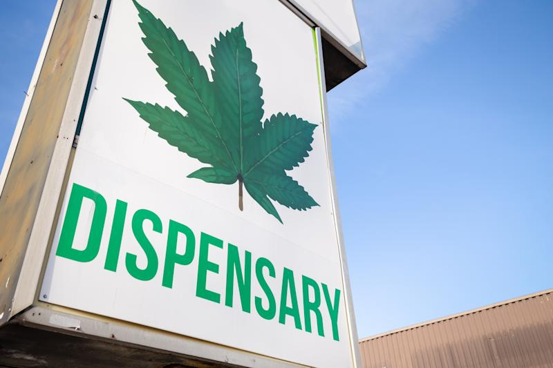 A large marijuana dispensary sign, with a cannabis leaf and the word dispensary written underneath it.