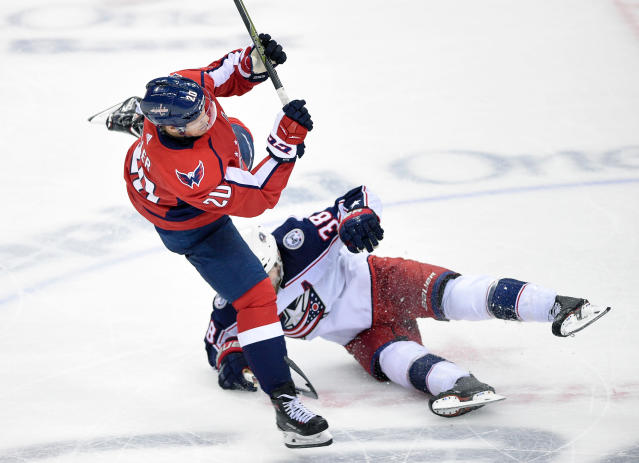 Washington Capitals center Lars Eller (20), of Denmark, gets tripped up against Columbus Blue Jackets center Boone Jenner (38) during the third period in Game 2 of an NHL first-round hockey playoff series, Sunday, April 15, 2018, in Washington. (AP Photo/Nick Wass)