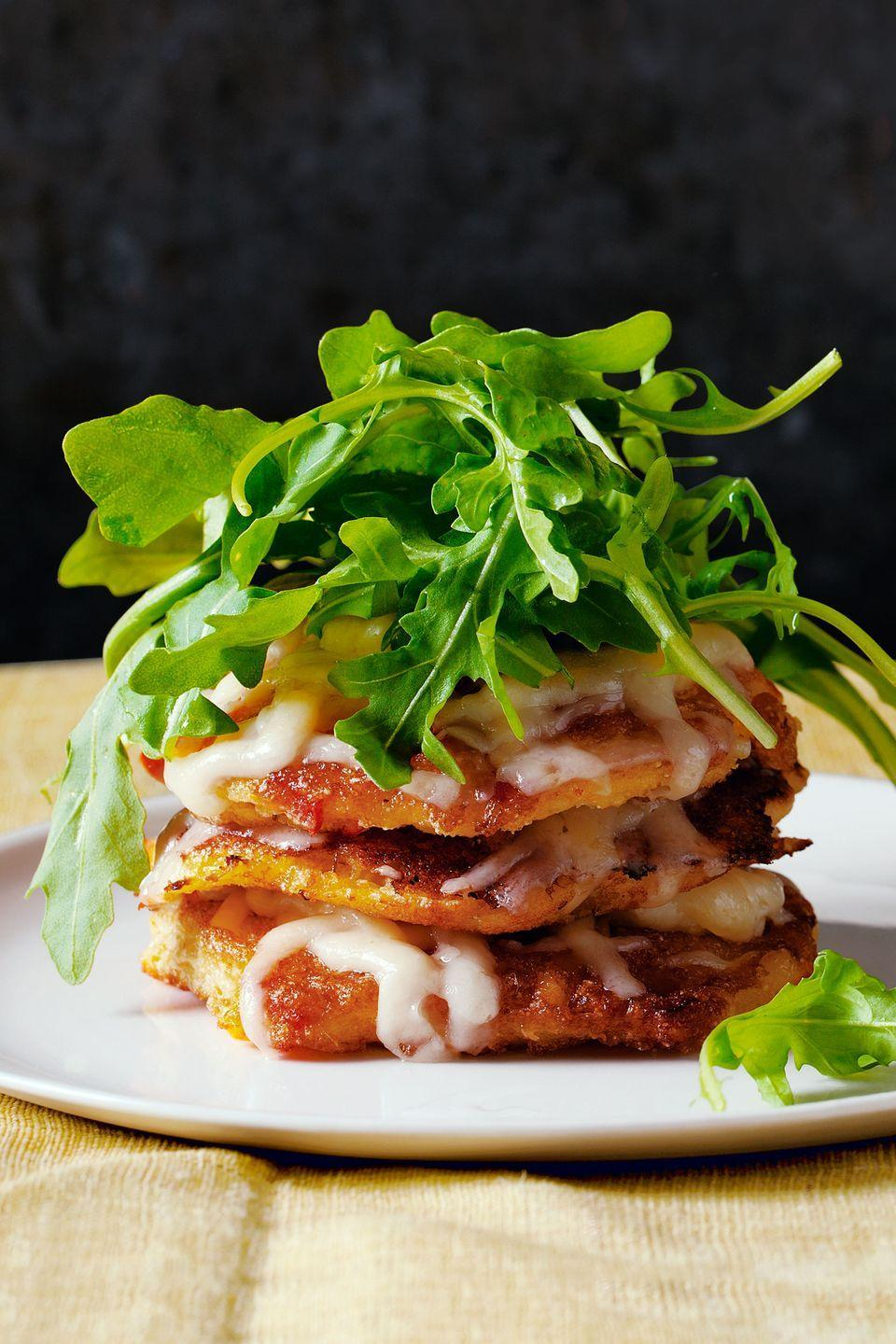 "Simple yet elegant, these sweet corn cakes topped with a fresh green salad and gooey Cheddar are the ideal summer dinner. <a href=""https://www.countryliving.com/food-drinks/recipes/a5275/corn-cake-stacks-aged-cheddar-arugula-recipe-clx0614/"" rel=""nofollow noopener"" target=""_blank"" data-ylk=""slk:Get the recipe."" class=""link rapid-noclick-resp""><strong>Get the recipe.</strong></a>"