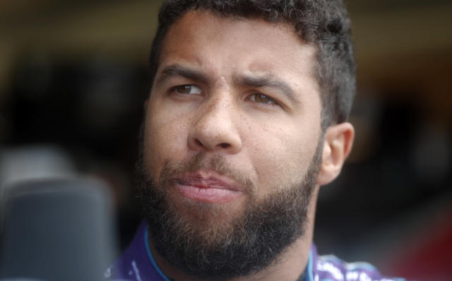 NASCAR driver Darrell Wallace Jr. speaks with a reporter before making a practice run for Sunday's NASCAR auto race Friday, Feb. 23, 2018, at Atlanta Motor Speedway in Hampton, Ga. (AP Photo/John Bazemore)