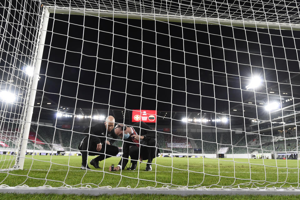 ST GALLEN, SWITZERLAND - MARCH 28: two men check the height of the goal during the FIFA World Cup 2022 Qatar qualifying match between Switzerland and Lithuania at Kybunpark on March 28, 2021 in St Gallen, Switzerland. (Photo by Urs Lindt-freshfocus/Getty Images)