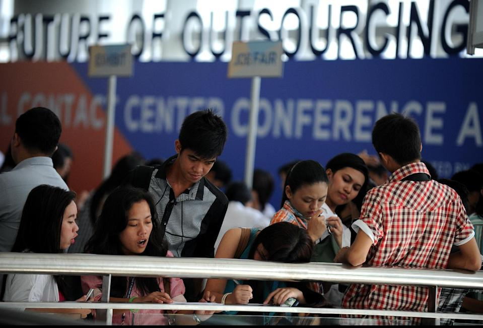Job seekers fill in their forms at a job fair for call centre agents at a conference in Manila on September 18, 2012 (AFP Photo/Noel Celis)