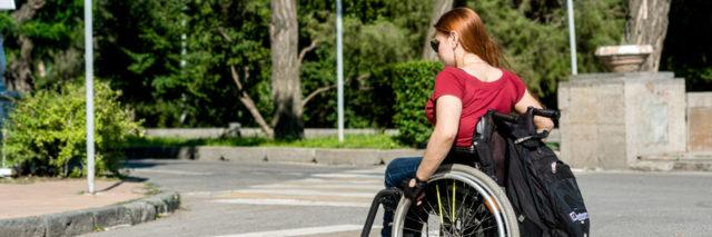 A young woman in a wheelchair at a pedestrian crossing.