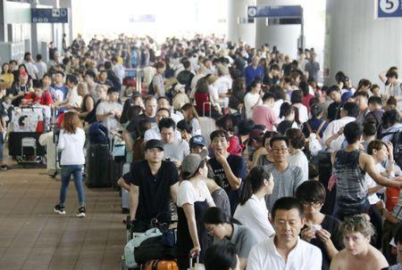 Passengers stranded at Kansai International Airport due to powerful typhoon Jebi queue outside the airport as they wait for the arrival of a special bus service to transport them out of the area, in Izumisato, western Japan, in this photo taken by Kyodo September 5, 2018. Mandatory credit Kyodo/via REUTERS