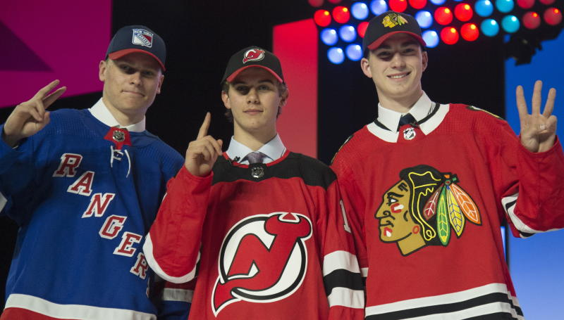 New York Rangers draft pick Kaapo Kakko, left; New Jersey Devils pick Jack Hughes, center; and Chicago Blackhawks pick Kirby Dach pose for photos during the first round of the NHL hockey draft Friday, June 21, 2019, in Vancouver, British Columbia. (Jonathan Hayward/The Canadian Press via AP)