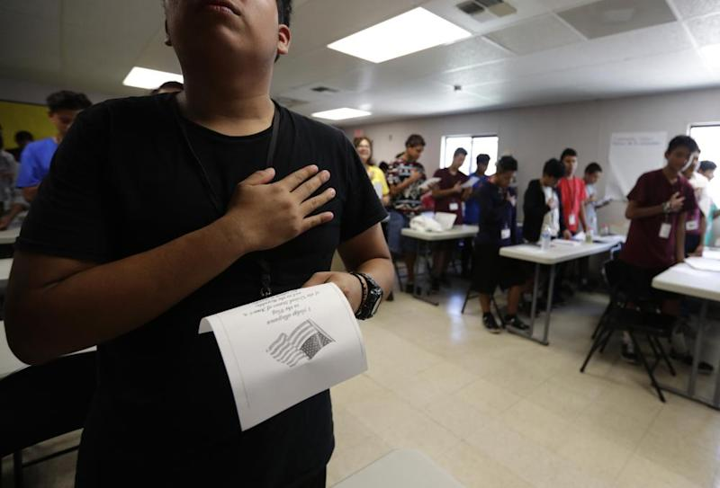 Immigrants say the Pledge of Allegiance in a writing class at the Carrizo Springs holding center in Texas.