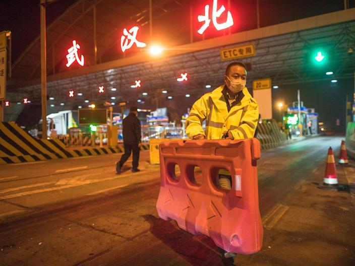 Staff members remove a barrier at a highway toll station in Wuhan on April 8, 2020.