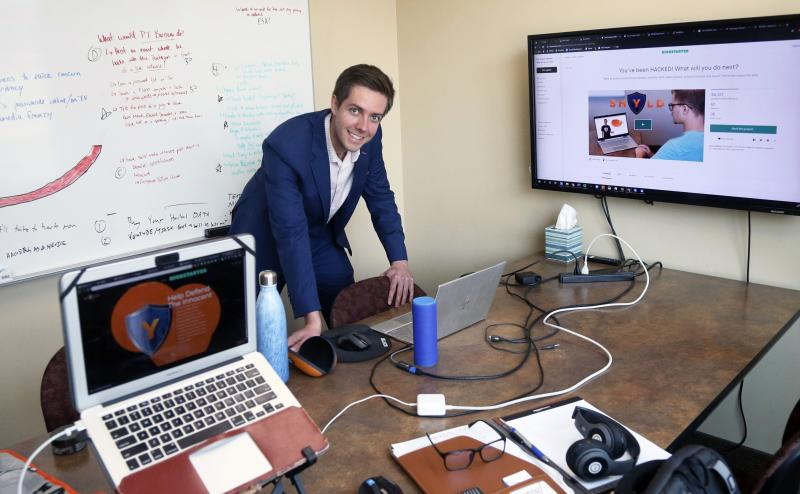 In this Aug. 27, 2019 photo, Tyler Olson poses in his office at the University of St. Thomas - Minneapolis campus. Olson is just starting a cybersecurity company. (AP Photo/Jim Mone)