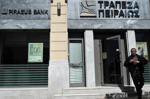A man leaves a branch of Piraeus Bank in central Athens on March 26, 2013