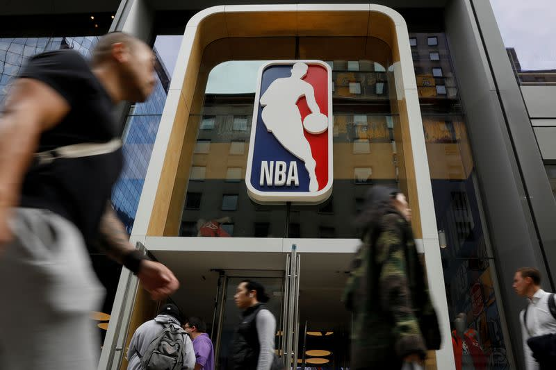 The NBA logo is displayed as people pass by the NBA Store in New York