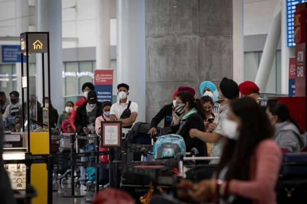 The last passengers from India and Pakistan to arrive at Toronto's Pearson airport wait to board buses to quarantine hotels on April 23, 2021. A 30-day federal ban on flights from India and Pakistan is in effect as COVID-19 cases in those countries continue to rise. (Evan Mitsui/CBC - image credit)