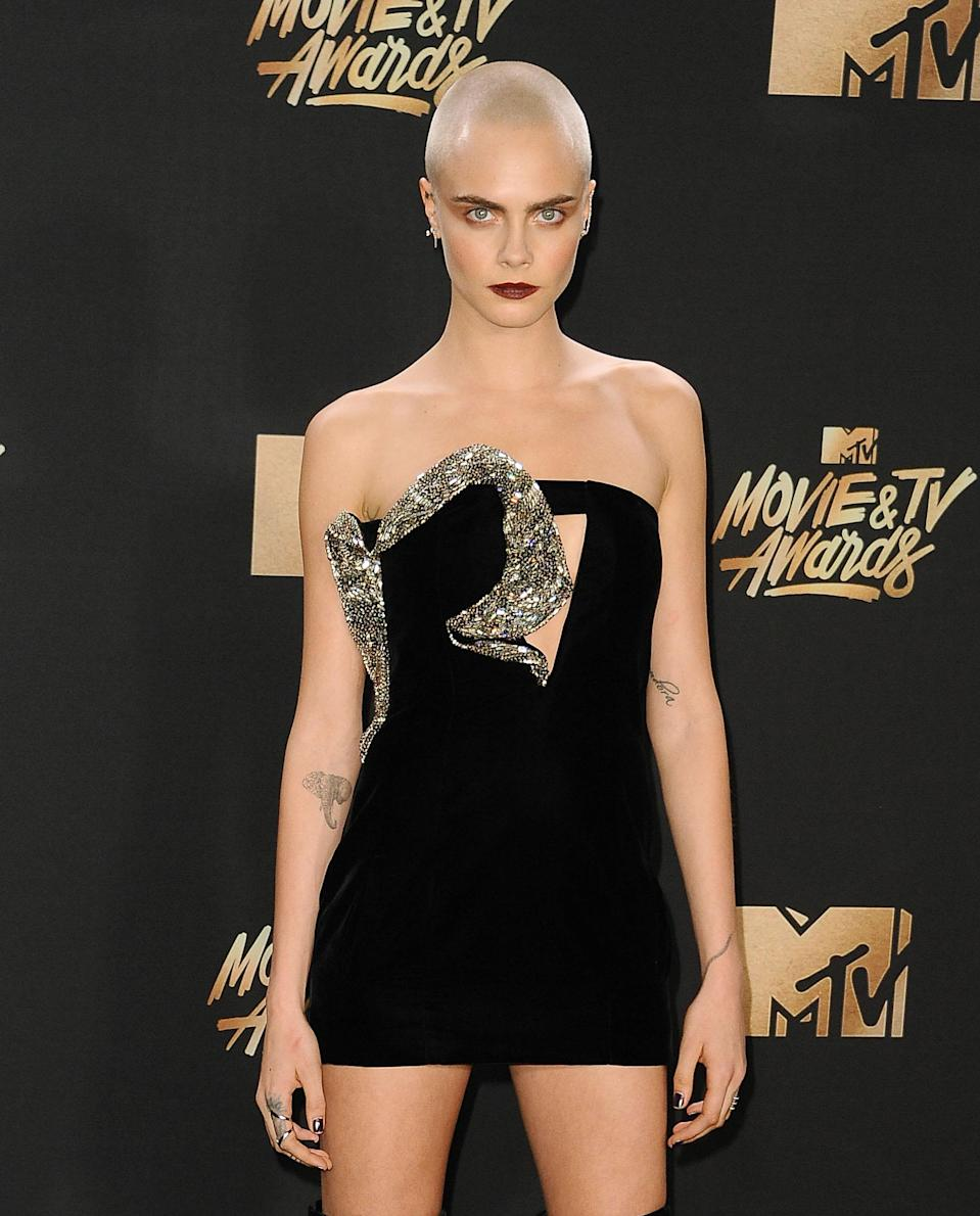 <p>Model Cara Delevingne reportedly has over 20 tattoos in total including a diamond in her ear and her mum's name Pandora on her inner left bicep. <em>[Photo: Getty]</em> </p>