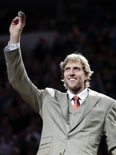 Dallas Mavericks' Dirk Nowitzki, of Germany, holds up his NBA championship ring during a ceremony before an NBA basketball game against the Minnesota Timberwolves, Wednesday, Jan. 25, 2012, in Dallas. (AP Photo/Tony Gutierrez)