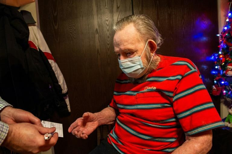 RN Todd Paul hands a CDC vaccine card to Gerald McDavitt, 81, a Veteran of the United States Army Corps of Engineers