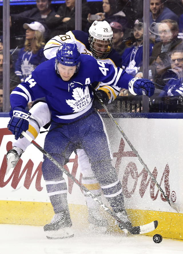 Toronto Maple Leafs defenseman Morgan Rielly (44) hits Buffalo Sabres centre Zemgus Girgensons (28) along the boards during first period NHL hockey action in Toronto on Monday, March 26, 2018. (Frank Gunn/The Canadian Press via AP)