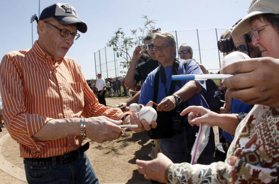 Los Angeles Dodger fan Larry King, left, signs autographs before a baseball game between the Arizona Diamondbacks and the Los Angeles Dodgers at Camelback Ranch Glendale Stadium on Tuesday March 10. 2009, in Phoenix. King, the suspenders-sporting everyman whose broadcast interviews with world leaders, movie stars and ordinary Joes helped define American conversation for a half-century, died Saturday, Jan. 23, 2021, at age 87. (Keith Birmingham/The Orange County Register/SCNG via AP)