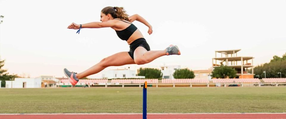 Fit female teenager athlete hurdler running jumping over hurdles