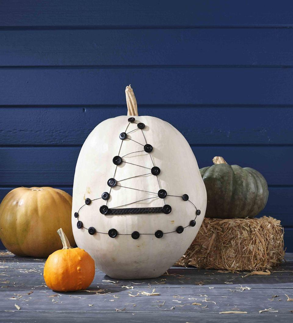 <p>An extra large pumpkin makes a perfect home for a witch hat made from buttons, string, and ribbon. Display on the front porch with a mini broom and bowl of candy!<strong><br></strong></p><p><strong>Make the pumpkin:</strong> Lightly draw a witch hat on a large white pumpkin. Attach thin black twine along drawing with hot-glue. Attach a length of twine in a zigzag pattern down the point of the hat with hot-glue. Attach medium-size buttons on top of string at even intervals and where the zigzag meets the outline with hot-glue.</p>