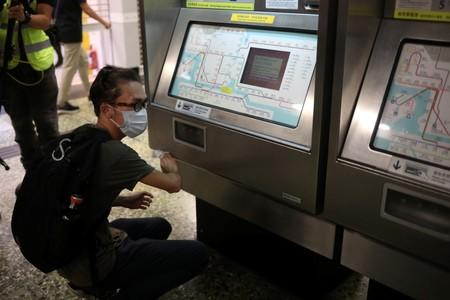 Supporter of the anti-extradition bill cleans the ticket machine as part of the Sham Shui Po Station Cleaning Campaign in Hong Kong