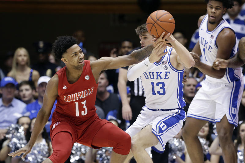 Louisville guard David Johnson (13) reaches for the ball while Duke forward Joey Baker (13) looks to pass it during the first half of an NCAA college basketball game in Durham, N.C., Saturday, Jan. 18, 2020. (AP Photo/Gerry Broome)