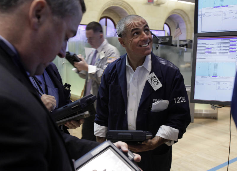 Trader Frank Cannarozzo smiles as he works on the floor of the New York Stock Exchange Friday, Aug. 3, 2012. U.S. stocks are rising sharply on Wall Street after a July jobs report revealed the strongest hiring trends in five months. (AP Photo/Richard Drew)