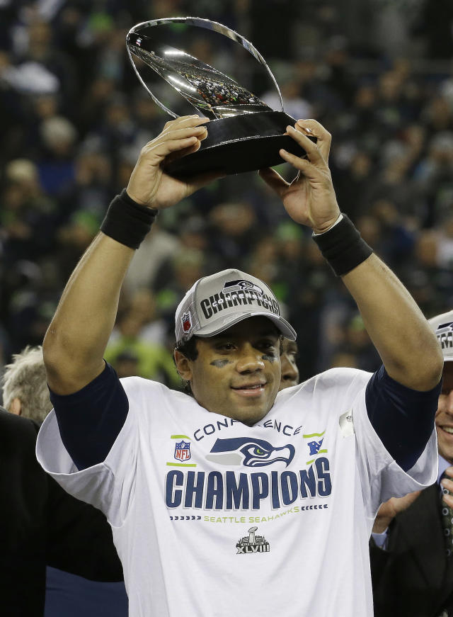 Seattle Seahawks' Russell Wilson holds up the George Halas Trophy after the NFL football NFC Championship game against the San Francisco 49ers Sunday, Jan. 19, 2014, in Seattle. The Seahawks won 23-17 to advance to Super Bowl XLVIII. (AP Photo/Ted S. Warren)