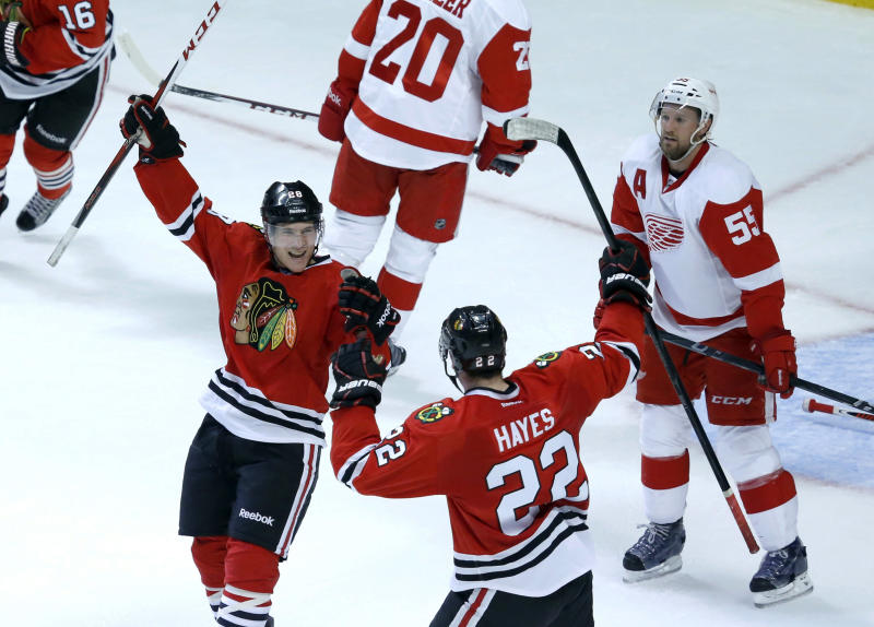 Chicago Blackhawks right wing Ben Smith, left, and right wing Jimmy Hayes (22) celebrate Smith's goal as Detroit Red Wings defenseman Niklas Kronwall watches during the second period of an NHL preseason hockey game Tuesday, Sept. 17, 2013, in Chicago. (AP Photo/Charles Rex Arbogast)