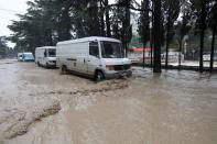 Vehicles are parked in a flooded street following heavy rainfall in Yalta