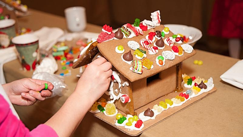 Child hands making Christmas holiday gingerbread cookie house.