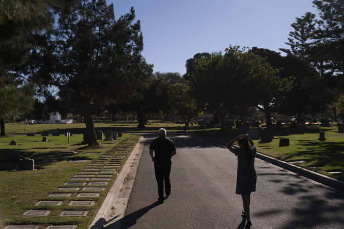 Clyde Matsumura is followed by daughter, Lilah, as he walks toward his father's grave after attending a memorial service for his grandfather, Giichi Matsumura, at Woodlawn Cemetery in Santa Monica, Calif., Monday, Dec. 21, 2020. Giichi Matsumura, who died in the Sierra Nevada on a fishing trip while he was at the Japanese internment camp at Manzanar, was reburied in the same plot with his wife 75 years later after his remains were unearthed from a mountainside grave. (AP Photo/Jae C. Hong)