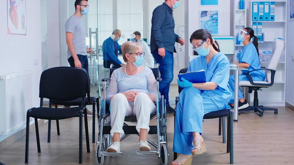 Nurse wearing face mask against coronavirus taking notes on clipboard while talking with disabled senior woman in wheelchair