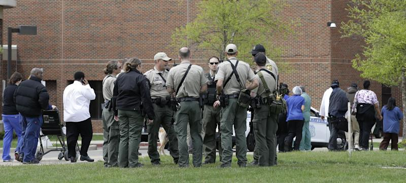 Police officials gather outside a Veterans Affairs hospital after people who were evacuated were told they could reenter the building, Monday, May 5, 2014, in Dayton, Ohio. A city official says a suspect is in police custody after a shooting at the hospital that left one person with a minor injury. (AP Photo/Al Behrman)