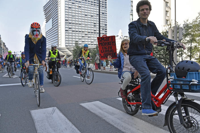 A small girl holds a sign as she rides on the back of a bicycle during a climate demonstration and march in Brussels, Sunday, Oct. 10, 2021. Some 80 organizations are joining in a climate march through Brussels to demand change and push politicians to effective action in Glasgow later this month.(AP Photo/Geert Vanden Wijngaert)