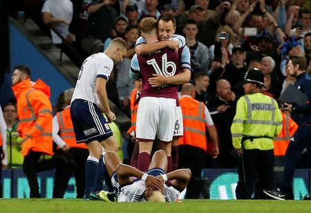 Soccer Football - Championship Play Off Semi Final Second Leg - Aston Villa v Middlesbrough - Villa Park, Birmingham, Britain - May 15, 2018 Middlesbrough's Adama Traore looks dejected as Aston Villa's John Terry and James Bree celebrate after the match Action Images via Reuters/Craig Brough