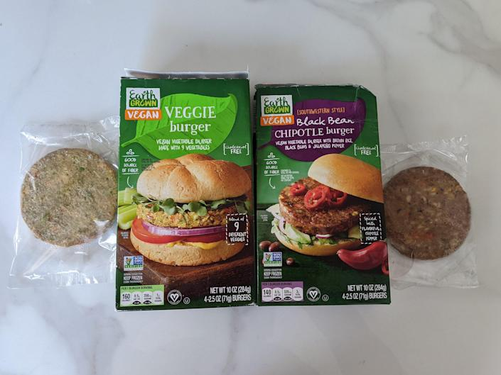 Aldi's veggie burgers in clear plastic and the two original green boxes on a white countertop