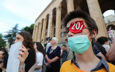 Protesters on Sunday wore eyepatches to reference two protesters who lost eyes in Thursday's demonstration as well as Russia's 'occupation' of 20 per cent of the country - Credit: Zurab Kurtsikidze/EPA-EFE/REX