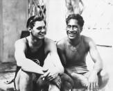 FILE - In this 1924 file photo, Johnny Weissmuller, left, and Duke Kahanamoku are seen at the 1924 Olympic games in Paris. For some Native Hawaiians, surfing's Olympic debut is both a celebration of a cultural touchstone invented by their ancestors, and an extension of the racial indignities seared into the history of the game and their homeland. Kahanamoku was a Native Hawaiian swimmer who won five Olympic medals and is known as the godfather of modern surfing who introduced the sport in surfing exhibitions in Australia and California. (AP Photo/File)