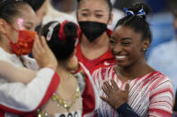 Simone Biles, of the United States, smiles as Tang Xijing, of China, left, embraces teammate Guan Chenchen after the latter won the gold medal on the balance beam during the artistic gymnastics women's apparatus final at the 2020 Summer Olympics, Tuesday, Aug. 3, 2021, in Tokyo, Japan. Biles won the bronze medal. (AP Photo/Natacha Pisarenko)