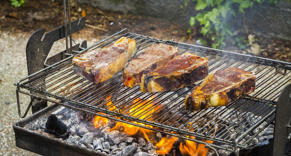 This image shows chops cooking on a charcoal barbecue.