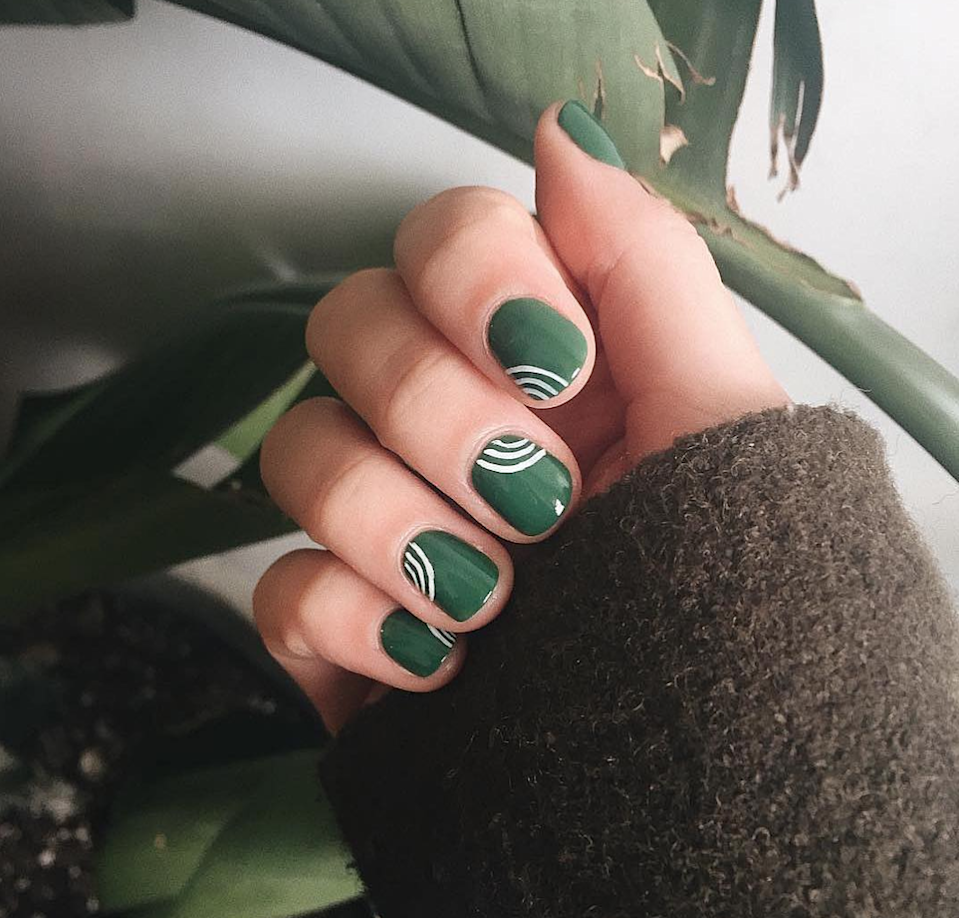 "Forest green screams ""fall,"" but it's a bit…predictable. Bring the shade up a notch with some graphic lines in crisp white. Try a paint pen like <a href=""https://www.target.com/p/sally-hansen-nail-art-pens-round-white/-/A-14777334"" rel=""nofollow noopener"" target=""_blank"" data-ylk=""slk:Sally Hansen Nail Art Pens"" class=""link rapid-noclick-resp"">Sally Hansen Nail Art Pens</a>, or just use a toothpick for the lines."