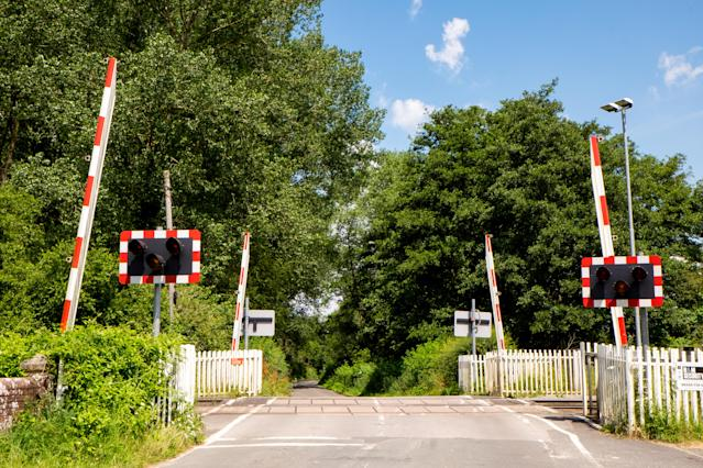 Country road with a railroad level crossing with the gates raised.