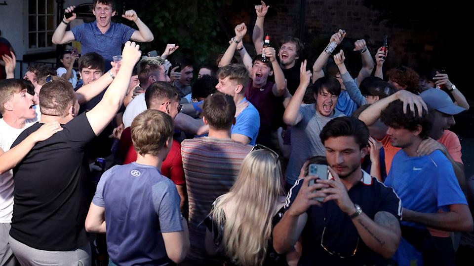 Fans, pictured here celebrating outside in Liverpool.