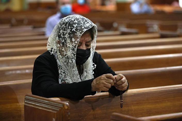 Sonia Rivas prays during Sunday Mass at St. Joseph's Catholic Church in Miami Beach on June 27, 2021. Some of the church's parishioners were among the missing after the condo collapse in nearby Surfside on Thursday, June 24.
