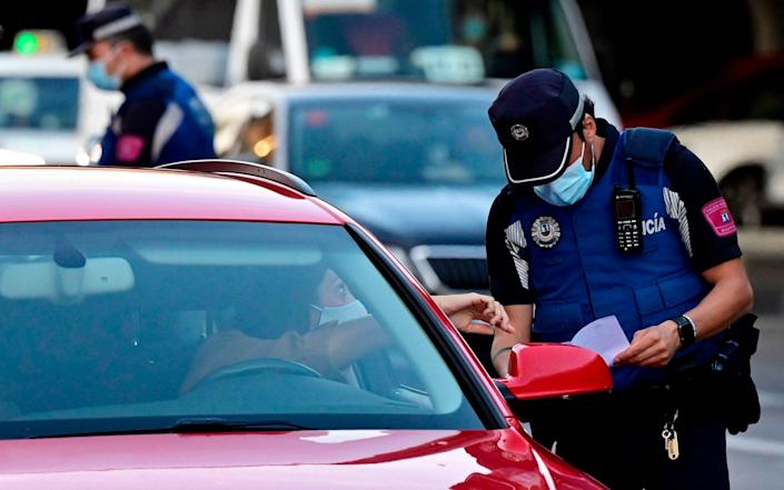 Local police monitor people's movements at a traffic checkpoint in the Puente de Vallecas neighbourhood - AFP