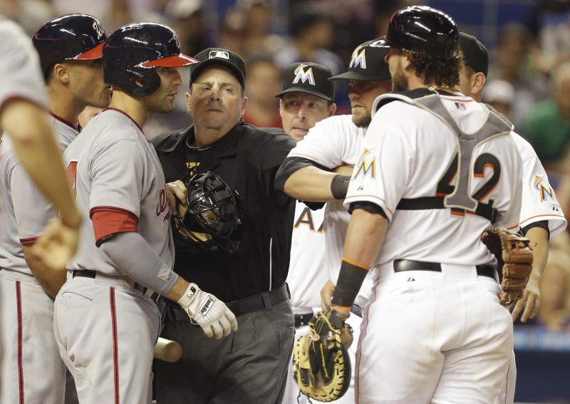 Home plate umpire Marty Foster, center, separates Washington Nationals' Ian Desmond, left, from Miami Marlins catcher Jarrod Saltalamacchia, right, during the fourth inning of the MLB National League baseball game, Tuesday, April 15, 2014, in Miami. Desmond had words with Saltalamacchia after the Miami Marlins starting pitcher Tom Koehler threw a close pitch. (AP Photo/Lynne Sladky)