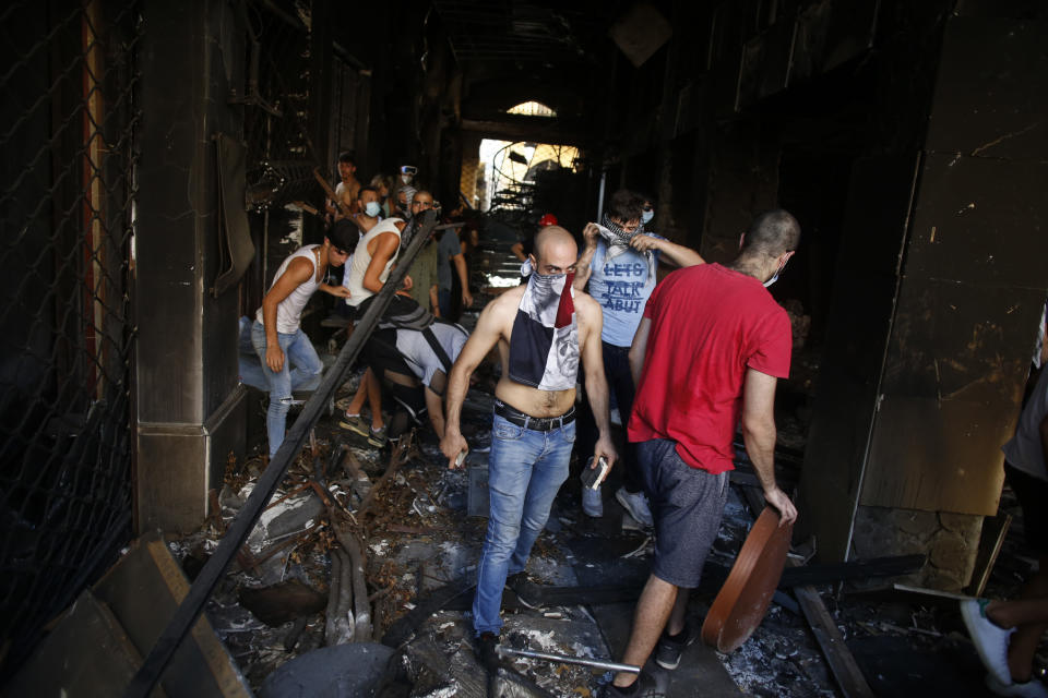 Protesters walk in an damaged building during clashes with police as part of a protest against the political elites and the government after this week's deadly explosion at Beirut port which devastated large parts of the capital in Beirut, Lebanon, Saturday, Aug. 8, 2020. (AP Photo/Thibault Camus)